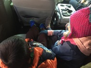 Selah rubbing Asher's leg in the van to make him feel better